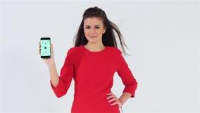 Χαμογελώντας όμορφο κορίτσι που εξετάζει τη κάμερα και το κράτημα του τηλεφώνου με το chromakey απόθεμα βίντεο