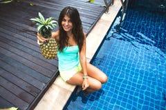 Χαμογελώντας όμορφο κορίτσι που παρουσιάζει ανανά Στοκ φωτογραφία με δικαίωμα ελεύθερης χρήσης