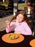 Χαμογελώντας όμορφο κορίτσι που τρώει την υγιή σαλάτα φρούτων υπαίθρια Στοκ Εικόνες