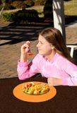 Χαμογελώντας όμορφο κορίτσι που τρώει την υγιή σαλάτα φρούτων υπαίθρια Στοκ Φωτογραφία