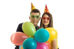Χαμογελώντας όμορφο νέο ζεύγος στα χρωματισμένα κρατημένα γυαλιά πολύχρωμα μπαλόνια Στοκ Φωτογραφία