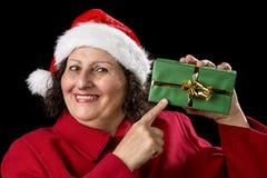 Χαμογελώντας ώριμη γυναίκα που δείχνει στο τυλιγμένο δώρο Χριστουγέννων στοκ εικόνες