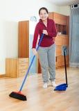 Χαμογελώντας ώριμη γυναίκα που σκουπίζει το πάτωμα Στοκ Εικόνες