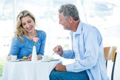 Χαμογελώντας ώριμος άνδρας που εξετάζει τη γυναίκα καθμένος Στοκ Εικόνα