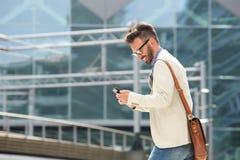 Χαμογελώντας ώριμος επιχειρηματίας που εξετάζει το κινητό τηλέφωνο Στοκ φωτογραφία με δικαίωμα ελεύθερης χρήσης