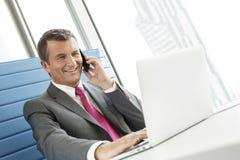 Χαμογελώντας ώριμος επιχειρηματίας που μιλά στο τηλέφωνο κυττάρων χρησιμοποιώντας το lap-top στην αρχή Στοκ Εικόνα