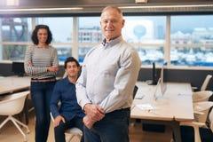Χαμογελώντας ώριμος διευθυντής σε ένα γραφείο με τους συναδέλφους πίσω από τον Στοκ Εικόνα