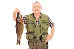 Χαμογελώντας ώριμος ψαράς που κρατά ένα μεγάλο ψάρι Στοκ Φωτογραφίες
