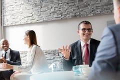 Χαμογελώντας ώριμο άτομο που μιλά με τον άνδρα συνάδελφος στην καφετέρια γραφείων στοκ εικόνες με δικαίωμα ελεύθερης χρήσης