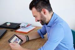 Χαμογελώντας ώριμο επιχειρησιακό άτομο που χρησιμοποιεί την ψηφιακή ταμπλέτα στο γραφείο Στοκ Φωτογραφία