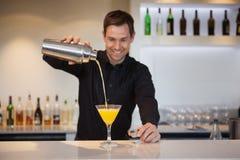 Χαμογελώντας bartender που χύνει το κίτρινο κοκτέιλ στο γυαλί Στοκ Εικόνες