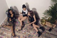 Χαμογελώντας multiethnic κορίτσια που κάθονται και που πίνουν τη σαμπάνια στο κόμμα Στοκ Εικόνες