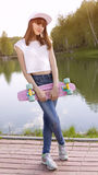 Χαμογελώντας skateboard εκμετάλλευσης κοριτσιών εφήβων Στοκ Εικόνα