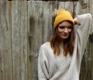 Χαμόγελα γυναικών σε ένα πουλόβερ και ένα καπέλο με ένα πυροβόλο στοκ εικόνες