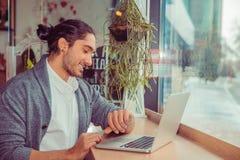 Χαμόγελο ατόμων που κοιτάζει στο wristwatch εργαζόμενων στον υπολογιστή στοκ εικόνες με δικαίωμα ελεύθερης χρήσης