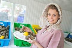Χαμόγελο θηλυκό ντύνω-επάνω στην πώληση των κατεψυγμένων θαλασσινών στην αγορά Στοκ φωτογραφία με δικαίωμα ελεύθερης χρήσης