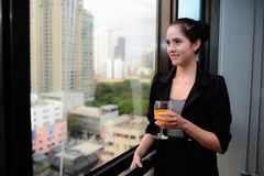 Χαμόγελο και στάση επιχειρησιακών γυναικών στο παράθυρο με τη σαμπάνια σε διαθεσιμότητα στοκ εικόνες