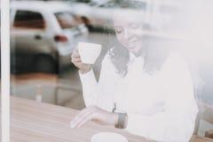 Χαμόγελο κορίτσι μόνη συνεδρίαση Φλυτζάνι του τσαγιού μιγάς στοκ φωτογραφία