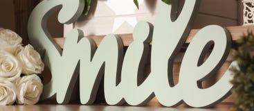 Χαμόγελο λέξης στο τρισδιάστατο ξύλο στην τυρκουάζ διακόσμηση χρώματος στοκ εικόνες