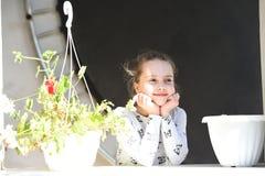 Χαμόγελο μικρών κοριτσιών με τα λουλούδια την ηλιόλουστη ημέρα Ευτυχές παιδί και παιδική ηλικία Παιδί ομορφιάς με τα δοχεία εγκατ Στοκ εικόνες με δικαίωμα ελεύθερης χρήσης