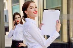 Χαμόγελο Νέο κορίτσι με έναν φάκελλο χαρτικών στα χέρια στο backg στοκ εικόνες με δικαίωμα ελεύθερης χρήσης