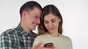 Χαμόγελο νεαρών άνδρων, που προσφέρει doughnut σοκολάτας στην όμορφη φίλη του φιλμ μικρού μήκους