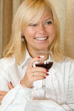 Χαμόγελο ξανθό με ένα ποτήρι του κόκκινου κρασιού Στοκ Φωτογραφίες