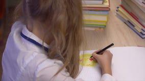 Χαμόγελο σχεδίων κοριτσιών στο copybook και συνεδρίαση στον πίνακα με τα βιβλία απόθεμα βίντεο
