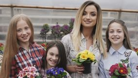 Χαμόγελο τεσσάρων κοριτσιών με flowerpots στα χέρια που εξετάζουν τη κάμερα απόθεμα βίντεο