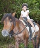 Χαμόγελο του αλόγου οδήγησης παιδιών στη φυσική ανασκόπηση Στοκ φωτογραφία με δικαίωμα ελεύθερης χρήσης