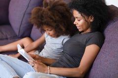 Χαμόγελο του βιβλίου ανάγνωσης μητέρων αφροαμερικάνων με την κόρη στοκ εικόνες