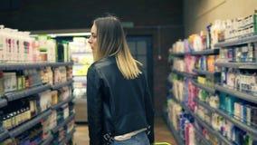 Χαμόγελο του καυκάσιου προϊόντος επιλογής γυναικών με το σαμπουάν από το ράφι στο τμήμα καλλυντικών στο κατάστημα Ξανθή γυναίκα π απόθεμα βίντεο