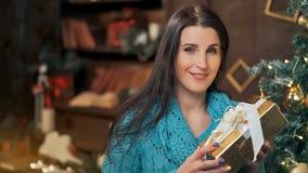 Χαμόγελο του κιβωτίου δώρων ανοίγματος γυναικών brunette πέρα από τα φω'τα του χριστουγεννιάτικου δέντρου απόθεμα βίντεο