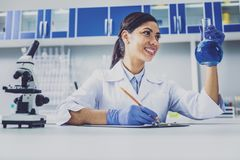 Χαμόγελο του σκοτεινός-μαλλιαρού βολβού εκμετάλλευσης φαρμακοποιών με το μπλε υγρό Στοκ Εικόνες