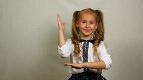Χαμόγελο του σχολικού αυξημένου κορίτσι βραχίονα για να απαντήσει σε μια ερώτηση, πυροβολισμός στούντιο απόθεμα βίντεο