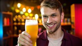 Χαμόγελο του τύπου που πίνει την ελαφριά μπύρα ξανθού γερμανικού ζύού που απολαμβάνει το γούστο, χόμπι των ατόμων, φεστιβάλ Οκτωβ στοκ εικόνες