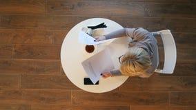 Χαμόγελο του όμορφου εγγράφου εκμετάλλευσης γυναικών στον καφέ στοκ φωτογραφία