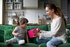 Χαμόγελο mom δίνοντας στο συγκινημένο παιδί το ανοικτό κιβώτιο δώρων με το παρόν στοκ φωτογραφία με δικαίωμα ελεύθερης χρήσης