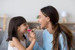 Χαμόγελο mom και ευτυχής κόρη παιδιών που κάνει makeup από κοινού στοκ εικόνες