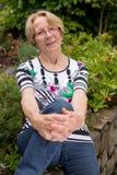 Χαμόγελα τα συμπαθητικά ηλικιωμένα γυναικών κάθονται στον κήπο και χαμογελούν στη κάμερα που κάμπτει ένα γόνατο και η κλίση σε το Στοκ φωτογραφία με δικαίωμα ελεύθερης χρήσης