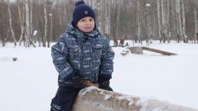 Χαμόγελο λίγου χαριτωμένου αγοριού seesaw κούτσουρων κατά τη διάρκεια των χιονοπτώσεων στο χειμερινό πάρκο απόθεμα βίντεο