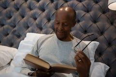 Χαμόγελο ανώτερων eyeglasses εκμετάλλευσης ατόμων διαβάζοντας το βιβλίο στην κρεβατοκάμαρα Στοκ Φωτογραφία