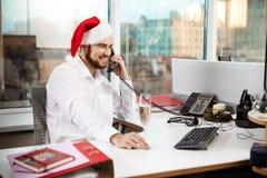 Χαμόγελο επιχειρηματιών που μιλά στο τηλέφωνο στη ημέρα των Χριστουγέννων worplace Στοκ Εικόνες