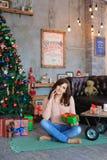 Χαμόγελο, συνεδρίαση και τοποθέτηση κοριτσιών στο καρό με το κιβώτιο δώρων υπό εξέταση στοκ φωτογραφίες