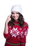 Χαμόγελο της αρκετά προκλητικής νέας γυναίκας που φορά το ζωηρόχρωμο πλεκτό πουλόβερ με τη διακόσμηση και το καπέλο Χριστουγέννων Στοκ Φωτογραφίες