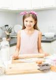 Χαμόγελο της κυλώντας ζύμης κοριτσιών στην ακατάστατη κουζίνα Στοκ εικόνες με δικαίωμα ελεύθερης χρήσης