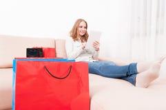 Χαμόγελο της ταμπλέτας εκμετάλλευσης γυναικείων αγοραστών που βάζει στον καναπέ Στοκ Φωτογραφία