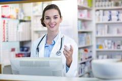 Χαμόγελο του εμπορευματοκιβωτίου ιατρικής εκμετάλλευσης φαρμακοποιών στο φαρμακείο στοκ εικόνες