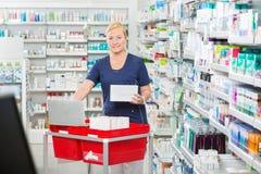 Χαμόγελο του ενημερώνοντας αποθέματος φαρμακοποιών στο lap-top στο φαρμακείο στοκ φωτογραφίες
