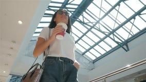 Χαμόγελο του καφέ κατανάλωσης γυναικών περπατώντας στο σύγχρονο πανεπιστημιακό, ευτυχή σπουδαστή στην αρχή ή λεωφόρος ή αερολιμέν απόθεμα βίντεο